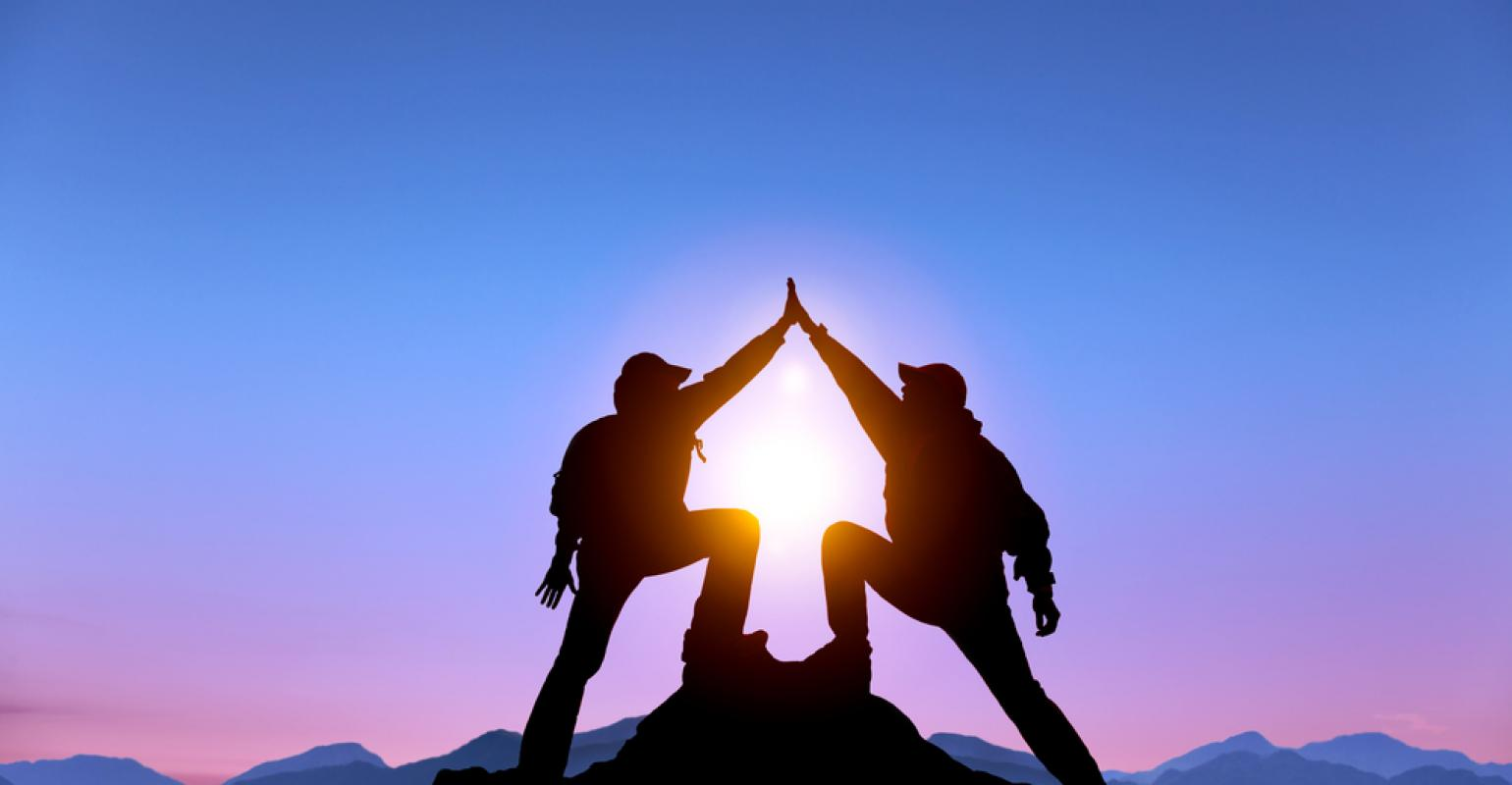 two man success on mountain top